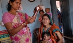 Health worker in India prepares to vaccinate baby