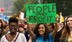 A young woman holds a People over Profit banner at a demonstration