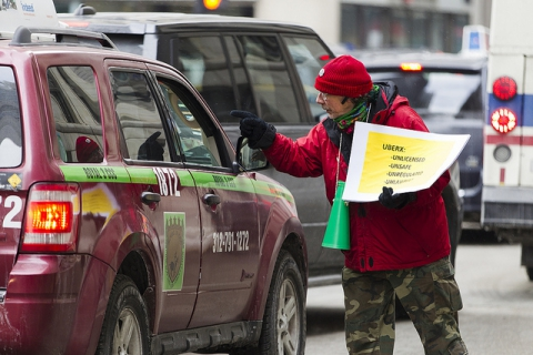 Taxi drivers have a discussion in the street during a protest over Uber outside City Hall in Chicago