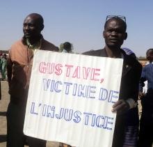 """Deux hommes portant un notice """"Gustave, victime de l'injustice"""""""