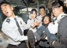 Korean police dragging away a female protestor