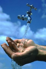 hands under a water tap against a blue sky
